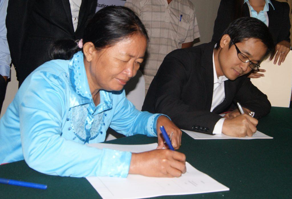 Die Vorsitzende einer Bauerngenossenschaft und AMRU-Geschäftsführer Song Saran unterzeichnen einen Vertrag © Winfried Scheewe