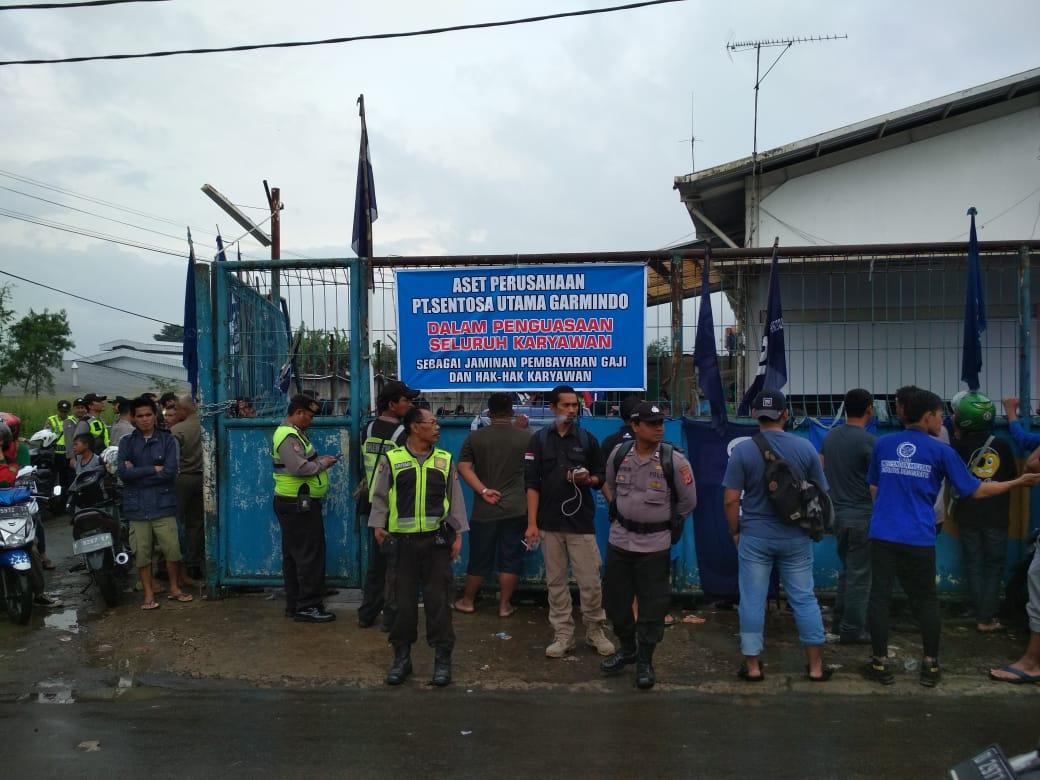 Die Polizei überwacht die Lage während die Arbeiter*innen das Fabrikgelände PT Sentosa Utama Garmindos besetzen © LIPS