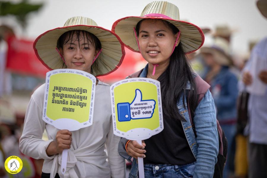 """Zwei Teilnehmerinnen halten im Freedom Park Protestschilder hoch: """"Zusammen für den Schutz fundamentaler Arbeitsrechte und für den Schutz des Arbeitsmarktes"""" (links) """"Feier den 133. Internationalen Tag der Arbeit"""" (rechts) © Central"""