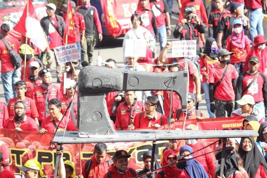 Eine riesige Nähmaschine, die von Gerakan Buruh untuk Rakyat (Gebrak – Arbeiterbewegung für das Volk) in der 1. Mai-Demonstration in Jakarta getragen wird. Die Nähmaschine symbolisiert die Produktionsmittel der Arbeiter*innen v.a. in der Bekleidungsindustrie, wo die Ausbeutung sehr hoch ist. © Dina Septi Utami/LIPS