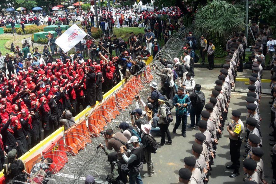 Arbeiter*innen der Föderation Verschiedener Industriezweige (FSPASI), eine Abspaltung von dem in der Suharto-Ära gegründete Staatsgewerkschaft SPSI, marschieren zum Palast des Präsidenten in Jakarta. Ihr Weg wird durch Stacheldraht und Polizisten blockiert © Marulloh, 2019