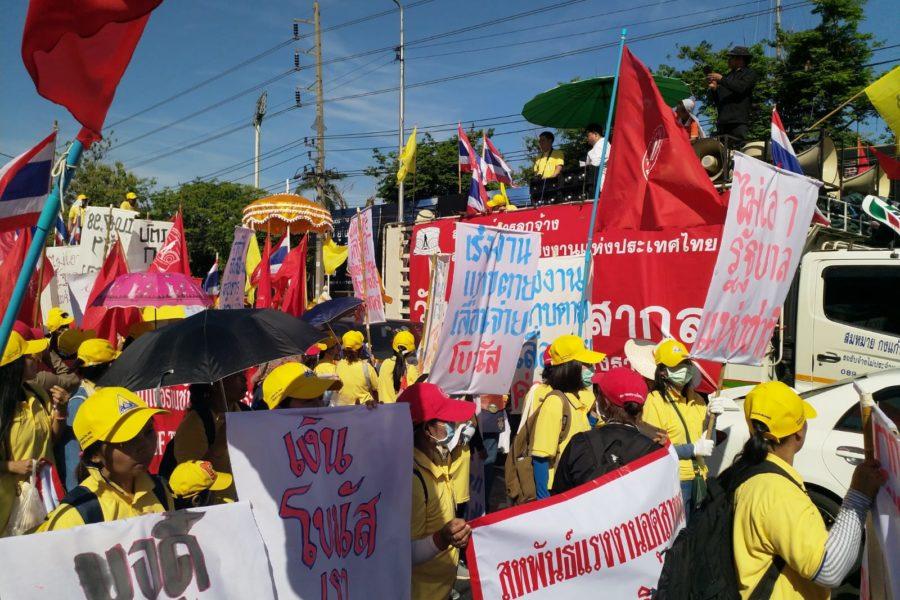 """Gelb und Rot. Die gelben Hemden sind vorgeschrieben, aber die Mützen, Transparente und Fahnen sind eher rot. Auf einem selbst gemachten Plakat ist zu lesen: """"Wir wollen keine Regierung der nationalen Einheit."""" Die Arbeiterin protestiert gegen den Vorschlag, eine Regierung aller """"nationalen"""" (= pro-militärischen) Kräfte unter Beteiligung nicht gewählter Politiker und Generäle zu bilden. © Patchanee Kumnak, 2019"""
