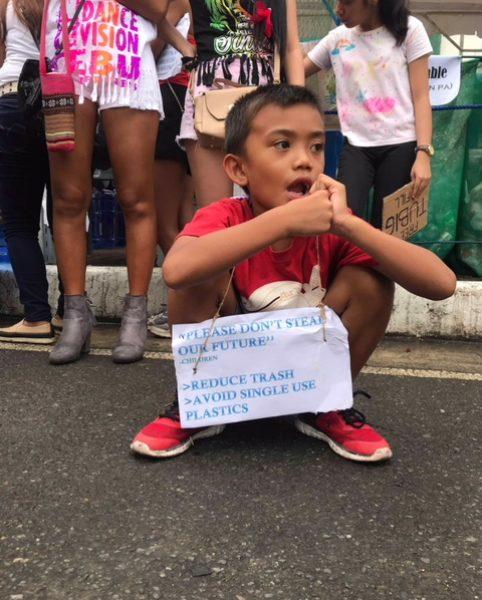 """""""Please don't steal our future"""" – So macht dieser kleine Junge die Besucher*innen des Festivals auf bewussten Plastikkonsum aufmerksam © Alieth Bontuyan"""