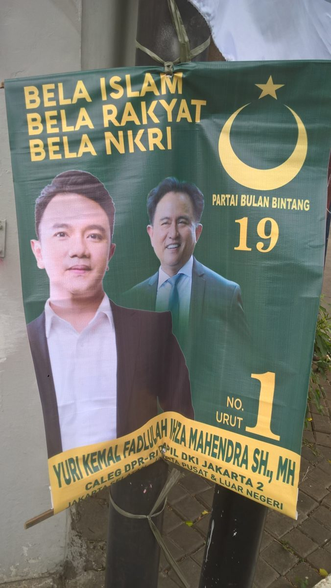 """Doch das Fischen nach Wähler*innenstimmen in konservativen islamischen Kreisen ging noch weiter: Auch Parteien, die Jokowi unterstützten, machten sich die Slogans zunutze, die einst von den Anhänger*innen der Anti-Ahok-Bewegung geprägt wurden. Die Kandidat*innen der PBB beispielsweise warben mit """"Verteidigt den Islam"""" (bela Islam) – ergänzt durch die patriotischen Slogans """"Verteidigt das Volk, verteidigt den Einheitsstaat der Republik Indonesien"""" (bela rakyat, bela NKRI). © Timo Duile"""